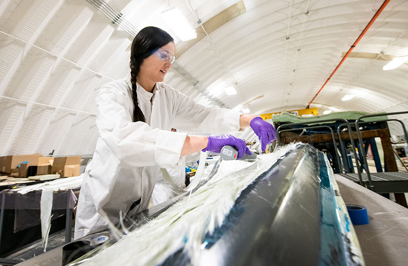 Woman in lab coat examines wind turbine blade